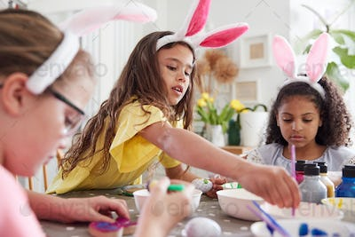 Three Girls Wearing Bunny Ears Sitting At Table Decorating Eggs For Easter At Home