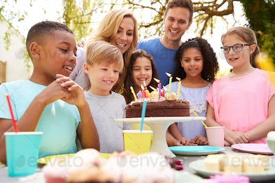 Parents And Son Celebrating Birthday With Friends Having Party In Garden At Home