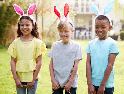 Portrait Of Three Children Wearing Bunny Ears On Easter Egg Hunt In Garden