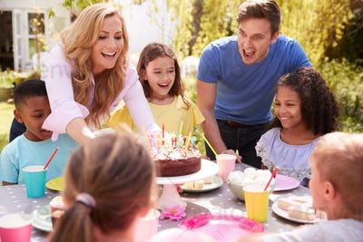 Parents And Daughter Celebrating Birthday With Friends Having Party In Garden At Home