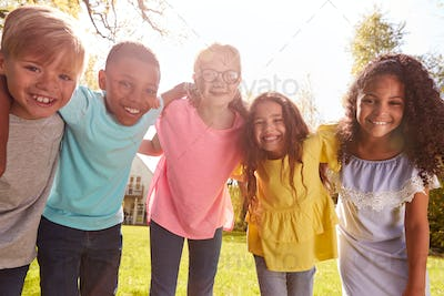 Portrait Of Smiling Children Outdoors At Home Looking Into Camera