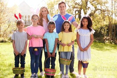 Portrait Of Parents With Children Wearing Bunny Ears On Easter Egg Hunt In Garden
