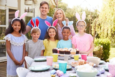 Portrait Of Parents With Children Wearing Bunny Ears Enjoying Outdoor Easter Party In Garden At Home