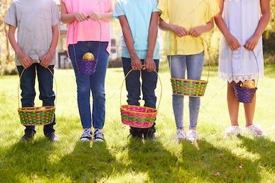 Close Up Of Five Children Holding Baskets On Easter Egg Hunt In Garden
