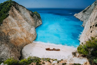 Epic view of Shipwreck middle of sandy Navagio beach surrounded by azure deep turquoise sea