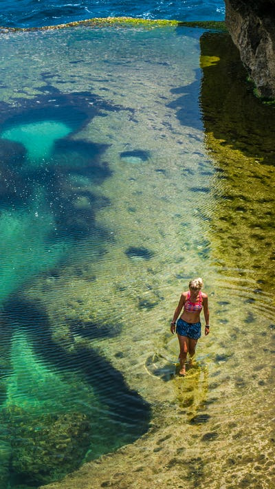 Girl walking in Natural Yellow Pool in Beautiful Cliff Formation, Bizarre Place, Nusa Penida Bali