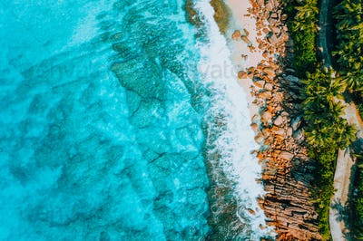Aerial bird eye shot of tropical coastline with tropical rocky beach and palm trees at Seychelles