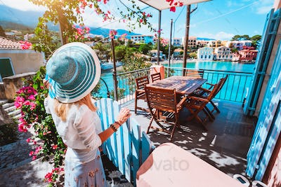 Female tourist with blue sun hat staying in Assos village in front of cozy veranda and admiring