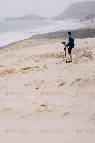 Photographer with camera in desert admitting unique landscape of sand dunes volcanic cliffs on the