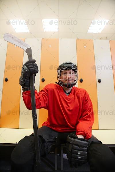 Female Hockey Player Posing in Locker Room