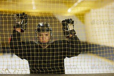 Female Hockey Player Posing by Net