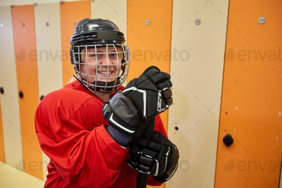 Smiling Hockey Player Posing in Locker Room