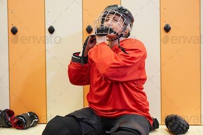 Female Hockey Player Getting Ready in Locker Room