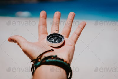 Open palm with stretched fingers holding black metal compass against white sandy beach. Find your