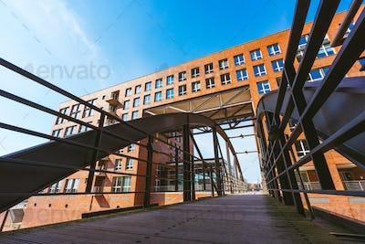 Famous landmark old Speicherstadt in Hamburg, build with red bricks. Bridge in low angle view