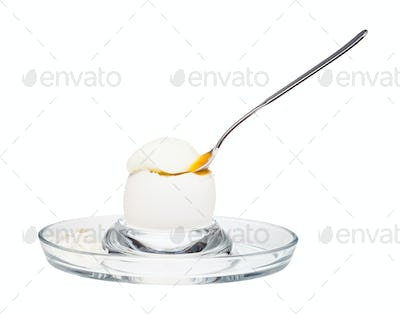 side view of soft-boiled egg with spoon in egg cup