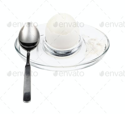 peeled boiled white egg and spoon in glass egg cup