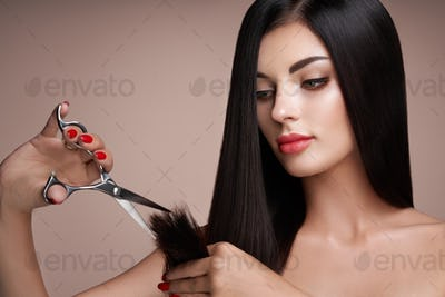 A young woman cutting her hair