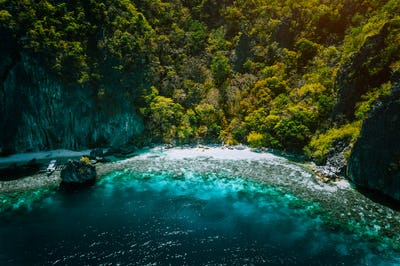 El Nido, Palawan, Philippines, aerial view of banca boat, karst mountain wall pristine sand beach