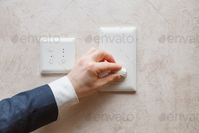 Man regulating temperature on air conditioning controller thermostat on the wall