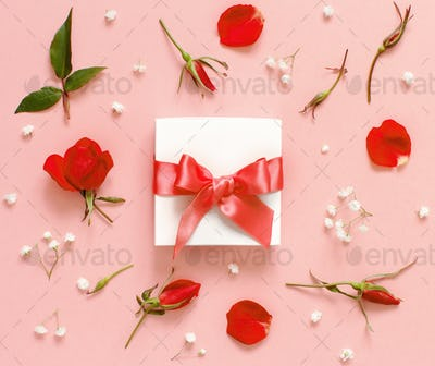 White gift box and flowers on a light pink background