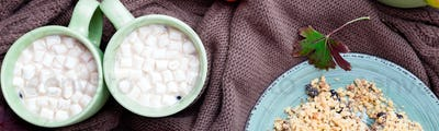Banner of Two cup of coffee or hot chocolate with marshmallow near knitted blanket.