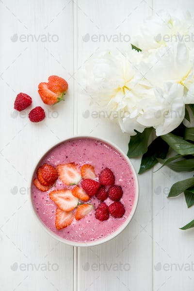 Healthy Pink Smoothie in the Bowl from Banana and Strawberries with Pieces of Berries on Top