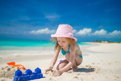 Little cute girl playing with beach toys during tropical vacation