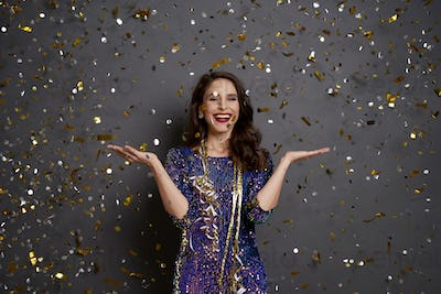 Woman holding something on her hand under shower of confetti