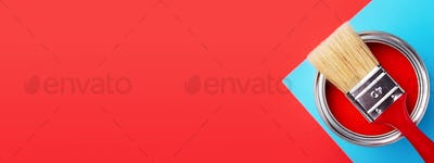 Can of Red Paint with Brush on Red and Blue Background. Banner.