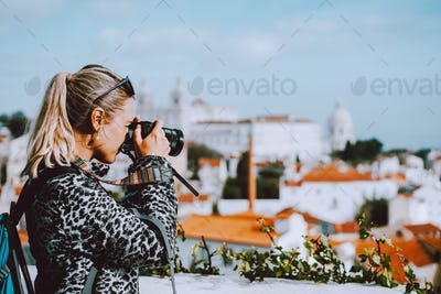 Traveler woman make a picture of Lisbon cityscape. The National Pantheon and the towels of Vicente