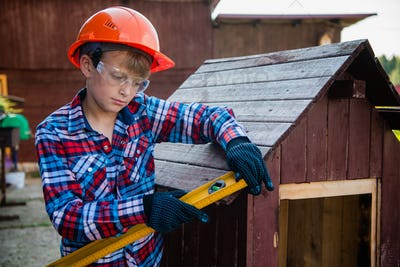 The boy holds the building level, checking the accuracy of the dog house roof