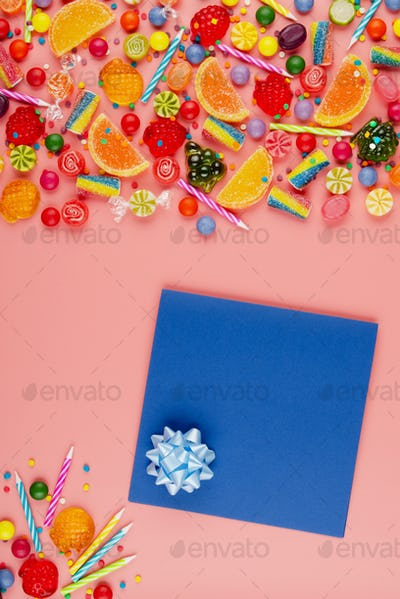Flat lay view at sweet background of greeting card and different type color and taste candies