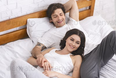 Happy spouses relaxing in bed and enjoying closeness