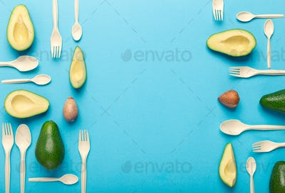 Forks and spoons of avocado seeds creative pattern on blue