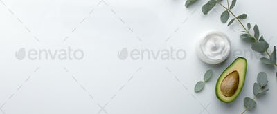 Cosmetic jar of facial cream with fresh avocado on white table