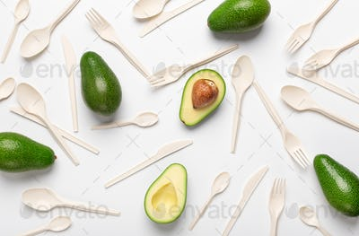 Halves of avocado and eco disposable tableware isolated on white