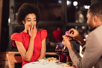 Man Proposing To Woman Offering Engagement Ring During Date Indoor