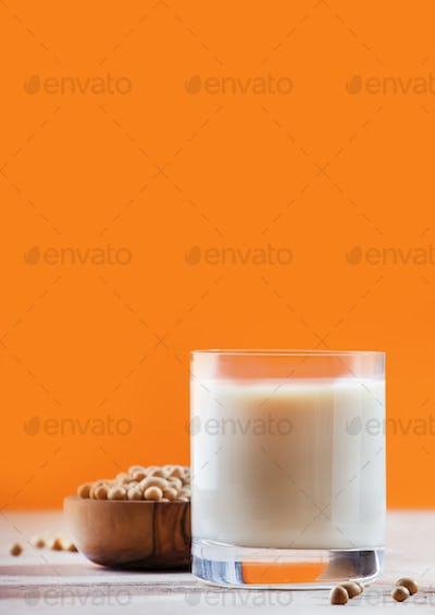 Soy milk and soy bean on orange background