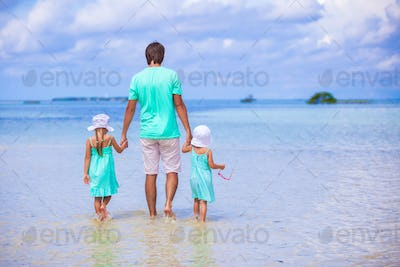 Adorable little girls and young father during beach vacation