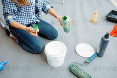 Female house painter mixes paints