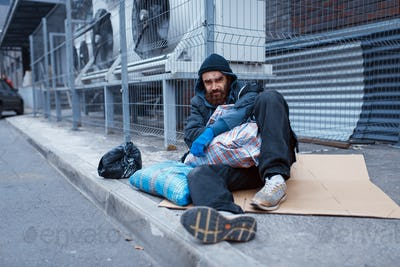 Male bearded beggar lies on city street