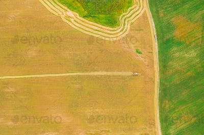 Aerial View Of Rural Landscape. Combine Harvester Working In Field, Collects Seeds.