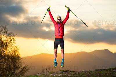 Sports man makes a jump in the mountains