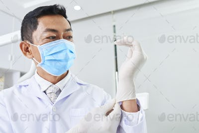 Dentist Putting On Latex Gloves