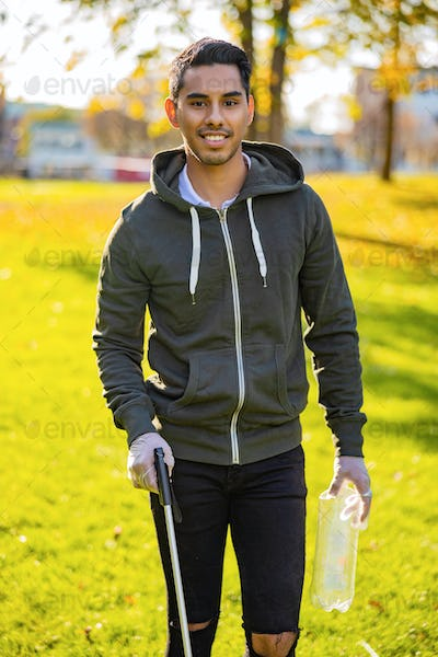 Confident young man cleaning park on sunny day