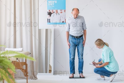 Middle age man standing on a weight scale while visiting a dietitian office