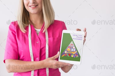 Pretty blonde nurse in pink uniform with tablet, copy space on empty white wall