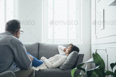 Woman at therapy room, laying on couch, discussing with psychotherapist her problems