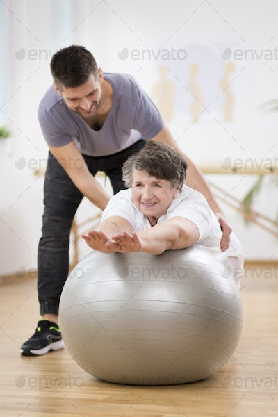 Smiling physiotherapy student helping senior woman lay on the exercising ball during rehabilitation